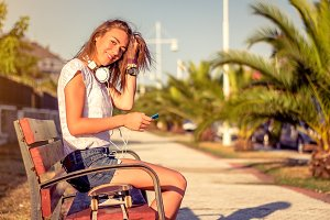 Young girl with skate and headphones