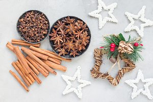 Different kinds of aromatic winter spices in bowls and on table, christmas decoration on a gray concrete background, horizontal