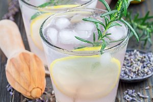 Homemade lemonade with lavender, fresh lemons and rosemary on wooden background, square format