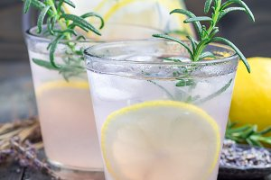 Homemade lemonade with lavender, fresh lemons and rosemary on a wooden background, square format