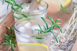 Homemade lemonade with lavender, fresh lemons and rosemary on a wooden tray, square format