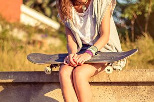 Young girl with skate sit on a wall
