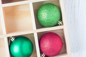 Preparation for Christmas: festive balls and candy cane in wooden box on a white table, square format