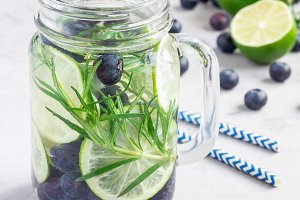 Healthy cold infused water with fresh blueberry, lime and rosemary, square format