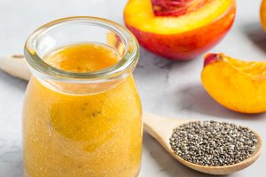 Smoothie with nectarine, orange juice, chia seeds and honey in glass jar, square