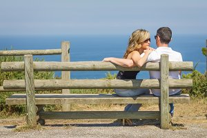Love couple sit outdoors on bench