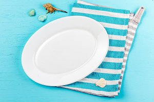 Food background in marine style. Marine table setting with white plate and sea decorations shells on wooden blue background. Top view, Copy space