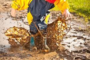 Child splashing in muddy puddle