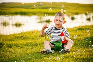 Boy sitting on green grass