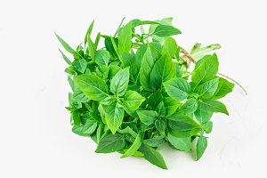 A bunch of green lemon basil on a white concrete table against a brick wall background