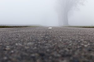 Asphalt road into the fog