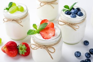 Yogurt with berries in glass jars