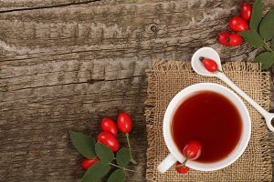 tea with rose hips and honey on old wooden background with copy space for your text. Top view