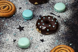 donuts with chocolate and macaroons on a dark background