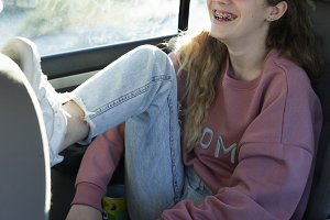 Teenager smiling inside a car.