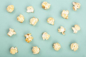 Popcorn on green background. Top view. Flat lay pattern