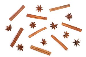 Composition of star anise and cinnamon sticks isolated on white. Abstract pattern flat lay, top view