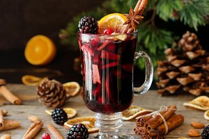 glass of hot mulled wine for the new year with ingredients for cooking, nuts and Christmas decorations