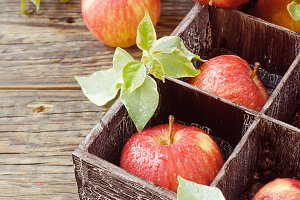 ripe red apples on wooden box on a rustic table, selective focus