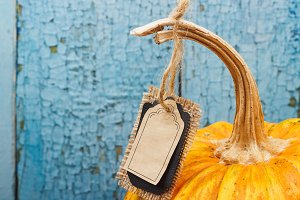 Orange pumpkin with decorative tag, wooden background