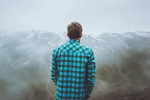 Man Traveler in foggy mountains