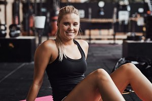 Young woman sitting in a gym smiling after working out