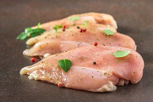 Raw fillet of chicken on rusty background. Meat ingredients for cooking.