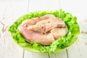 Raw chicken fillet and green salad in a yellow bowl on a white wooden table. Meat ingredients for cooking. Top view.