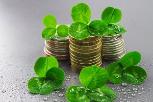 Stacks of Russian coins with clover leaves on a gray background with droplets of water. St.Patrick 's Day.