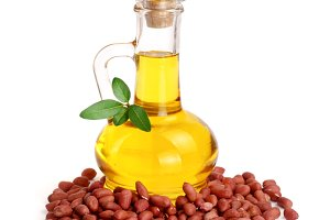 peanut oil in a glass bottle with peanuts