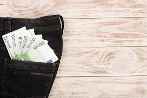 one hundred euro banknotes in a jeans pocket on white wooden background with copy space for your text. Top view