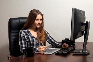 Retoucher young woman is sitting in front of computer