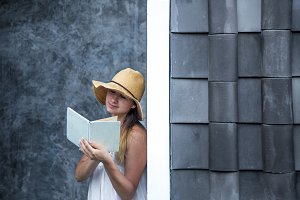 girl reading a book against a wall in the street
