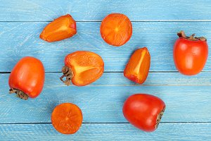 persimmon on blue wooden background. Top view. Flat lay pattern