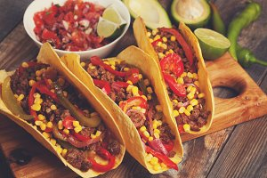Mexican tacos with minced beef, vegetables and salsa. Tacos al pastor on wooden rustic background