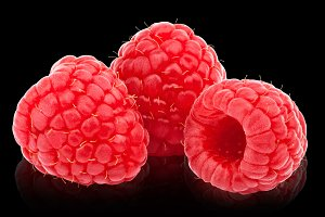 Three ripe raspberries isolated  on black