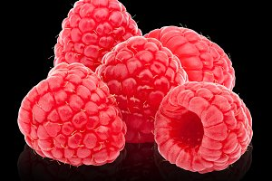 Five ripe raspberries isolated on black