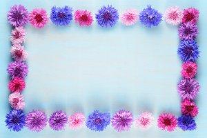 Flower frame of cornflowers on blue