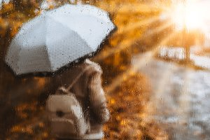 Beautiful golden autumn season. Watercolor like blurred blond girl with backpack and bright umbrella stands under rainy drops and droplets. Backlit sunset sun flares shining. Wet gray ground