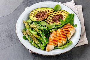 Healthy grilled chicken, grilled avocado and asparagus salad with linen seeds. Balanced lunch in bowl. Gray slate background. Top view