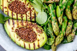 Healthy grilled avocado and asparagus salad with linen seeds. Gray slate background. Top view