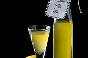Italian limoncello in a shot glass on a black wooden background
