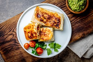 Mexican chimichanga on white plate served with guacamole sauce. Fried tortilla stuffed with chicken and vegetables. Traditional Mexican food, Top view