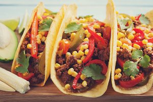 Mexican tacos with minced beef, vegetables and salsa. Tacos al pastor on wooden blue rustic background