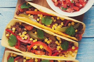 Mexican tacos with minced beef, vegetables and salsa. Tacos al pastor on wooden blue rustic background. Top view