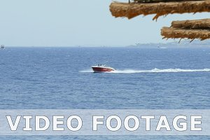 Powerboat ship sails along tropical resort beach
