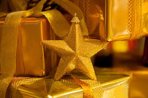 Close-up of golden Christmas star and gifts piled up in stack blurred - (selective focus)