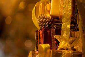 Close-up of golden gifts piled up in stack blurred in gold bokeh background - (selective focus)