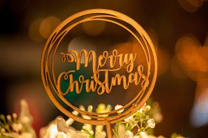 Merry Christmas text sign topper stick on the top of bouquets with xmas tree in the background bokeh