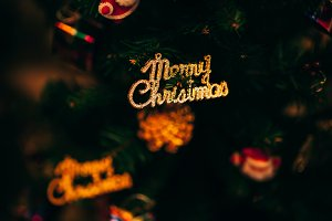 Merry Christmas text sign ornament attached on Xmas tree - selective focus